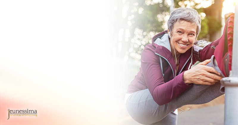 A mature woman is keeping herself fit and flexible to stay young and happy